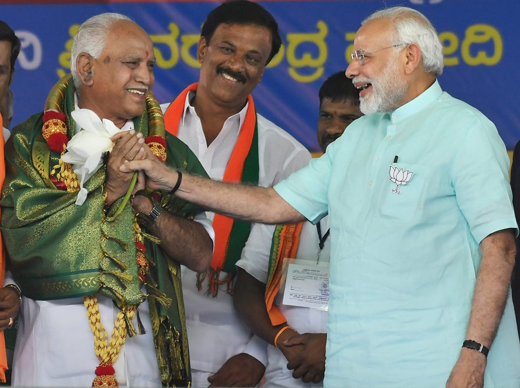 Chamarajanagar: Prime Minister Narendra Modi and BJP's chief ministerial candidate BS Yeddyurappa share a lighter moment during Karnataka election campaign rally at Chamarajanagar on Tuesday