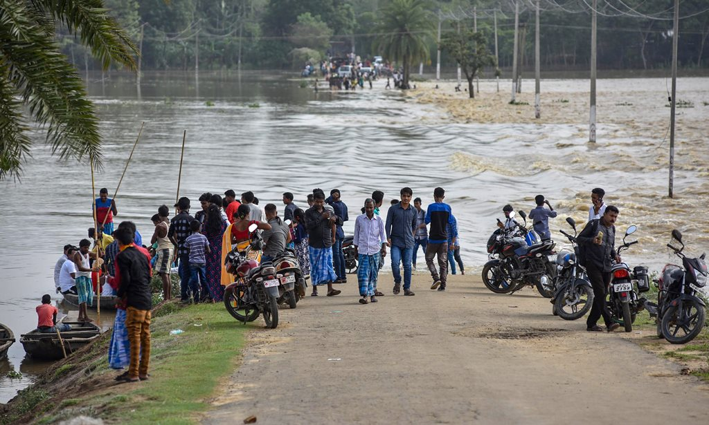 Hojai: Villagers stand near a partially-submerged land in the flood-affected area, of Hojai on Saturday, June 16, 2018. (PTI Photo) (PTI6_16_2018_000155B)