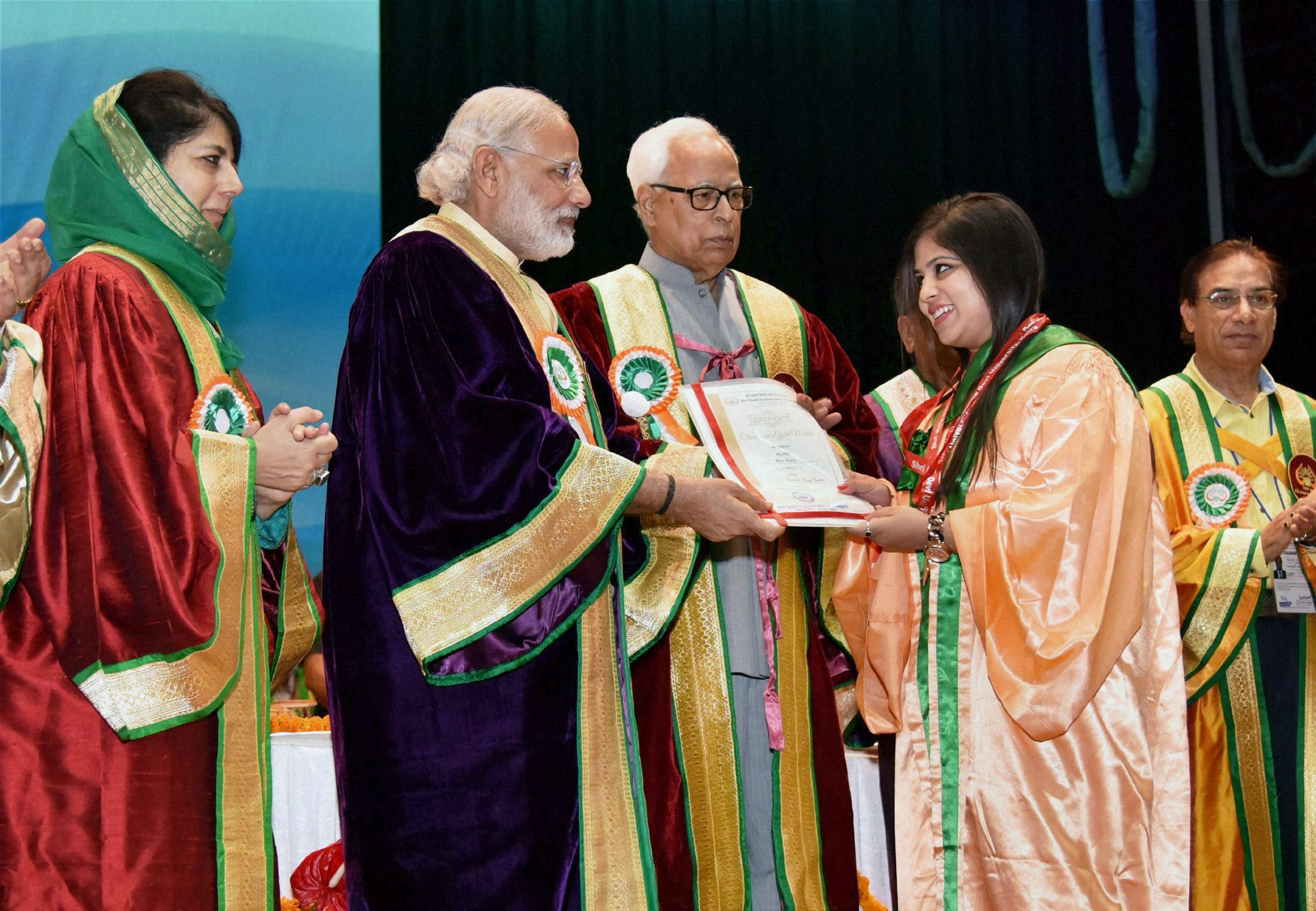 RPT:Jammu: Prime Minister Narendra Modi presents certificate to a student at the 5th Convocation of Shri Mata Vaishno Devi University at Katra in Jammu and Kashmir on Tuesday. Governor of Jammu and Kashmir, N N Vohra Jammu and Kashmir Chief Minister Mehbooba Mufti are also seen. PTI Photo (PTI4_19_2016_000028B)