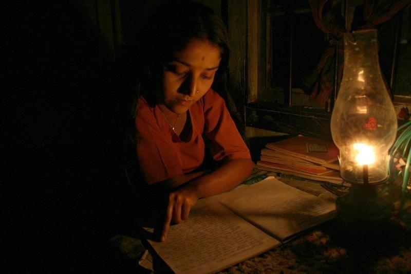 An Indian girl studies by kerosene lamp due to a power cut-off in the remote village of Lingsey, about 157 km (98 miles) from the northeastern Indian city of Siliguri, February 26, 2006. REUTERS/Rupak De Chowdhuri