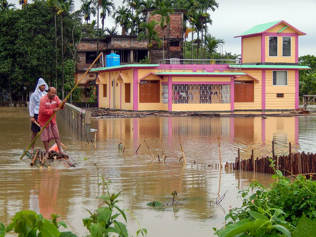 Unakoti: A villager rows his makeshift boat through the water at a flood-affected village of Unikuti district on Tuesday, June 12, 2018. (PTI Photo)(PTI6_12_2018_000242B)