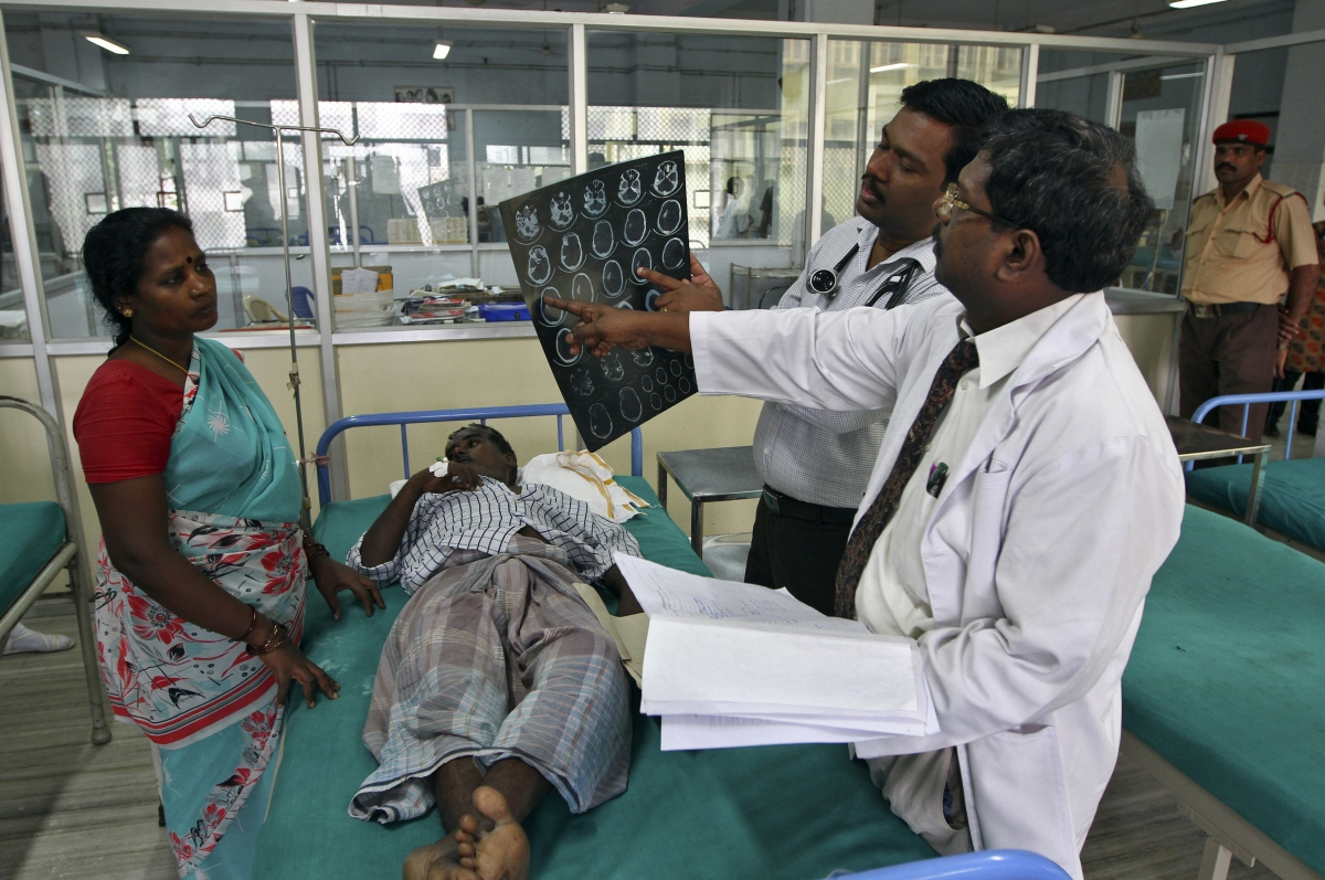 Doctors examine a magnetic resonance imaging (MRI) scan of a patient lying on a bed inside a ward at Rajiv Gandhi Government General Hospital (RGGGH) in Chennai July 12, 2012. REUTERS/Babu/Files