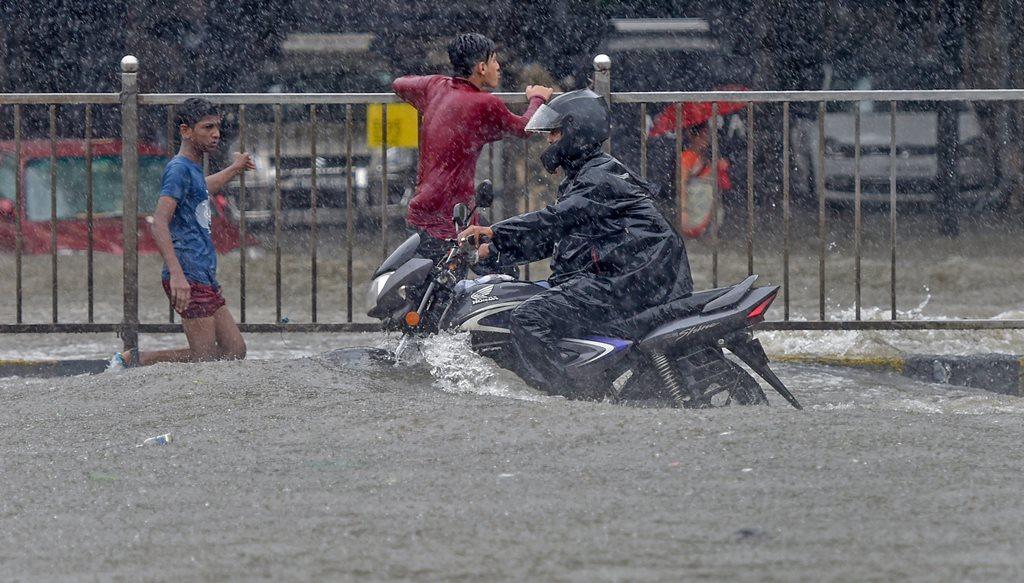 Mumbai: A motorcyclist moves through a waterlooged road during heavy rains, at King Circle in Mumbai on Tuesday, July 10, 2018. (PTI Photo/Shashank Parade) (PTI7_10_2018_000103B)