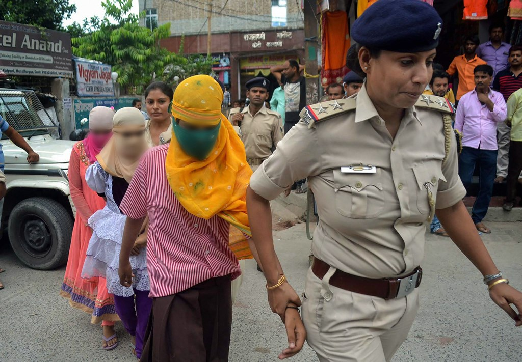 Muzaffarpur: Police personnel escort children out of a government-funded shelter, in Muzaffarpur, on Monday, July 23, 2018. A girl of a government shelter home has alleged that one of her fellow inmates was beaten to death and buried at the premises of the facility, and several were raped. (PTI Photo)(PTI7_23_2018_000192B)