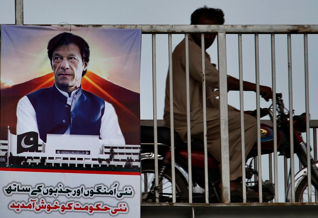 Islamabad: A motorcyclist moves past a poster with images of Imran Khan as it is displayed in the celebration of his government on a bridge in Islamabad, Pakistan, Saturday, Aug. 18, 2018.  Pakistan's cricket star-turned-politician Khan was sworn in as prime minister on Saturday despite protests by opposition parties, which accuse the security services of intervening on his behalf in last month's elections. The poster reads 'Welcome to this new government with new hopes and aspiration'. AP/PTI(AP8_18_2018_000041B)