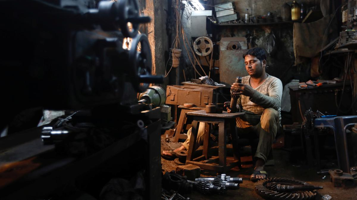 A man repairs gear parts used in automobiles inside a workshop at an industrial area in Mumbai, India. Small businesses have been struggling with the new tax. (Photo: Danish Siddiqui/Reuters)