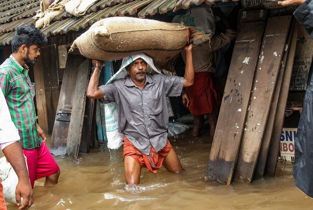 Kozhikode: A person carries a grain sack as his house gets flooded after Kakkayam dam was opened following heavy monsoon rainfall, in Kozhikode on Thursday, Aug 16, 2018. (PTI Photo) (PTI8_16_2018_000282B)
