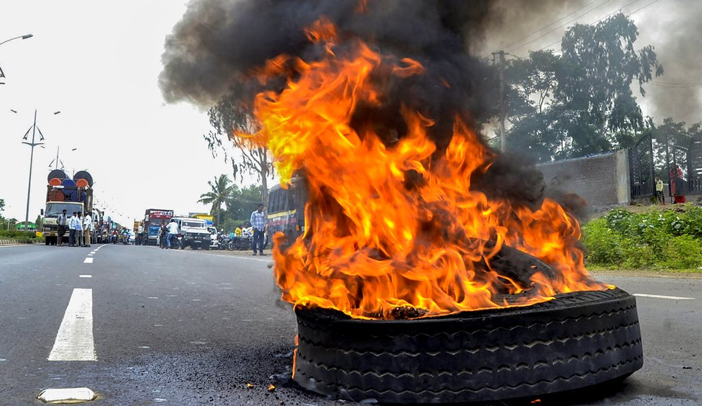 Solapur: Maratha Kranti Morcha activists burn a tyre to stop traffic during their district bandh called for reservations in jobs and education, in Solapur, Maharashtra on Monday, July 30, 2018. (PTI Photo) (PTI7_30_2018_000219B)