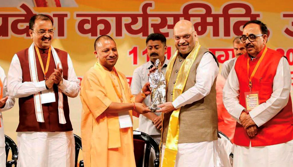 Meerut: BJP President Amit Shah is welcomed by UP Chief Minister Yogi Adityanath at the BJP's State Working Committee Meeting, in Meerut on Sunday, August 12, 2018. (Twitter Photo via PTI)(PTI8_12_2018_000150B)