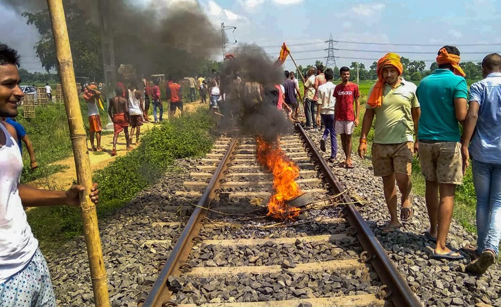 Patna: Swarn Sena activist burn tyres on the railway tracks to stop trains during their Bharat bandh, called to press for reservation, in Patna, Thursday, Sept 6, 2018. (PTI Photo) (PTI9_6_2018_000081B)