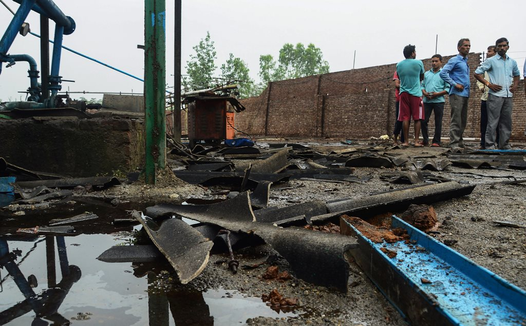 Bijnor: People stand near the site of explosion at a petro-chemical factory where a methane gas boiler tank exploded killing six workers, in Bijnor, Wednesday, Sep 12, 2018. (PTI Photo) (PTI9_12_2018_000079B)