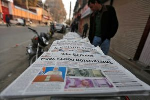 A man looks at newspapers with cover stories on withdrawal of Indian 500 and 1,000 rupee notes from circulation, on a pavement in Srinagar November 9, 2016. REUTERS/Danish Ismail