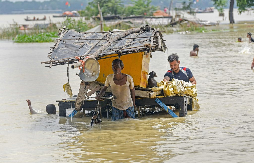 Allahabad: People move their belongings to a secure location as the water level of river Ganga rose creating a flood-like situation, in Allahabad, Tuesday, Sept 4, 2018. (PTI Photo) (PTI9_4_2018_000062A)(PTI9_4_2018_000185B)