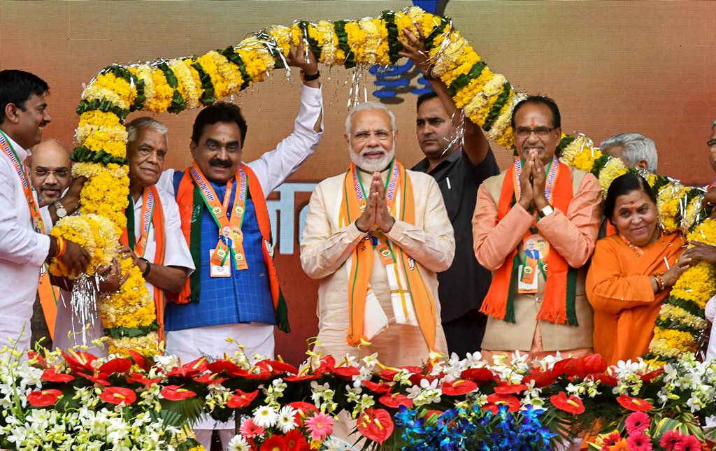 Bhopal: Prime Minister Narendra Modi being garlanded during BJP 'Karyakarta Mahakumbh', in Bhopal, Tuesday, Sept 25, 2018. (PTI Photo)(PTI9_25_2018_000114B)