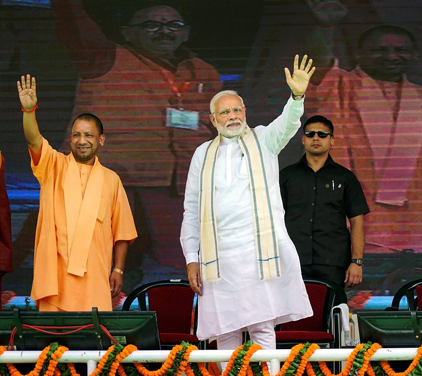 Varanasi: Prime Minister Narendra Modi and Uttar Pradesh Chief Minister Yogi Adityanath during a public meeting, in Varanasi, Tuesday, September 18, 2018. (PTI Photo)(PTI9_18_2018_000033B)