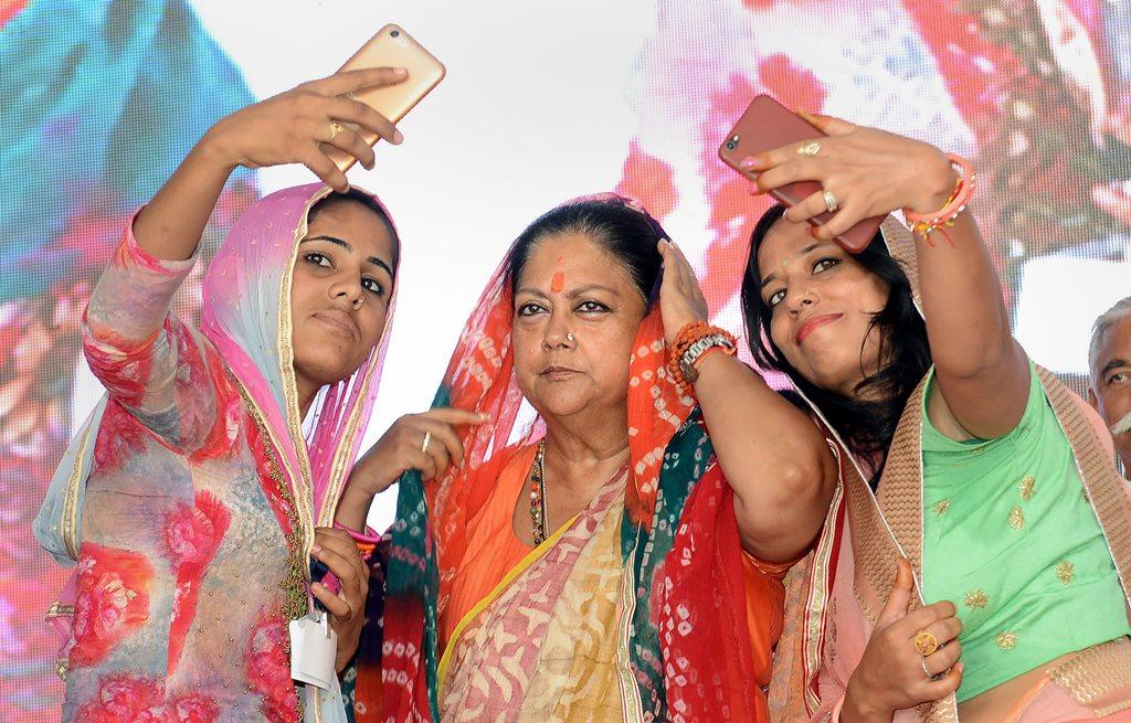 Barmer: Women take selfie with Rajasthan Chief Minister Vasundhara Raje during 'Rajasthan Gaurav Yatra' at Baytu, near Barmer on Sunday, Sept 2, 2018. (PTI Photo) (PTI9_2_2018_000122B)