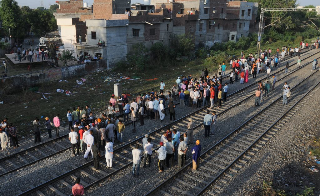 Amritsar: Punjab Police personnel and local people gather at the scene of the accident along train tracks in Amritsar, Saturday, October 20, 2018. A speeding train ran over revellers watching fireworks during the Dussehra festival Friday, killing more than 50 people. (PTI Photo) (PTI10_20_2018_000007B)