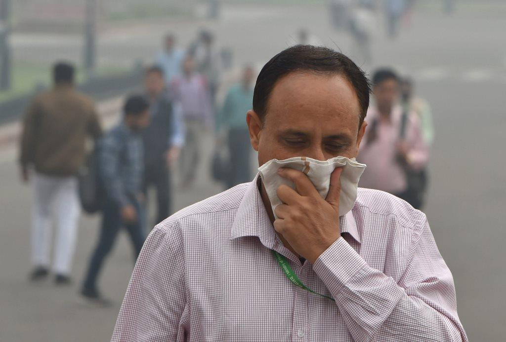 New Delhi: A pedestrian covers his face with a handkerchief for protection against air pollution, in New Delhi, Tuesday, Nov. 13, 2018. A thick haze engulfed the national capital today as the air quality remained in the 'severe' category and authorities expressed concern that light rainfall the city may worsen the pollution levels. (PTI Photo/Shahbaz Khan)(PTI11_13_2018_000025)