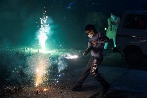 New Delhi: A boy wearing pollution mask burns crackers during Diwali celebrations, in New Delhi, Wednesday, Nov. 07, 2018. According to the officials, Delhi recorded its worst air quality of the year the morning after Diwali as the pollution level entered 'severe-plus emergency' category due to the rampant bursting of toxic firecrackers. (PTI Photo/Ravi Choudhary)(PTI11_8_2018_000023B)