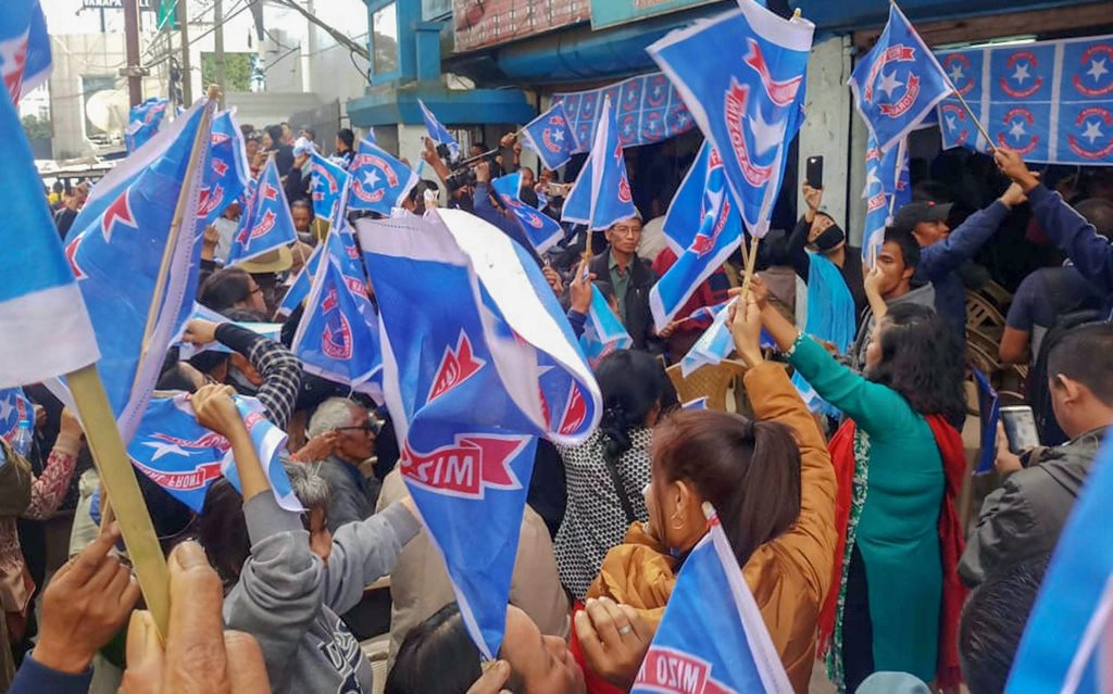 Aizawl: Mizo National Front (MNF) workers hold their party flag as they celebrate the party's victory in the states Assembly elections, at Party  head office, in Aizawl, Tuesday, Dec. 11, 2018. (PTI Photo)(PTI12_11_2018_000203)