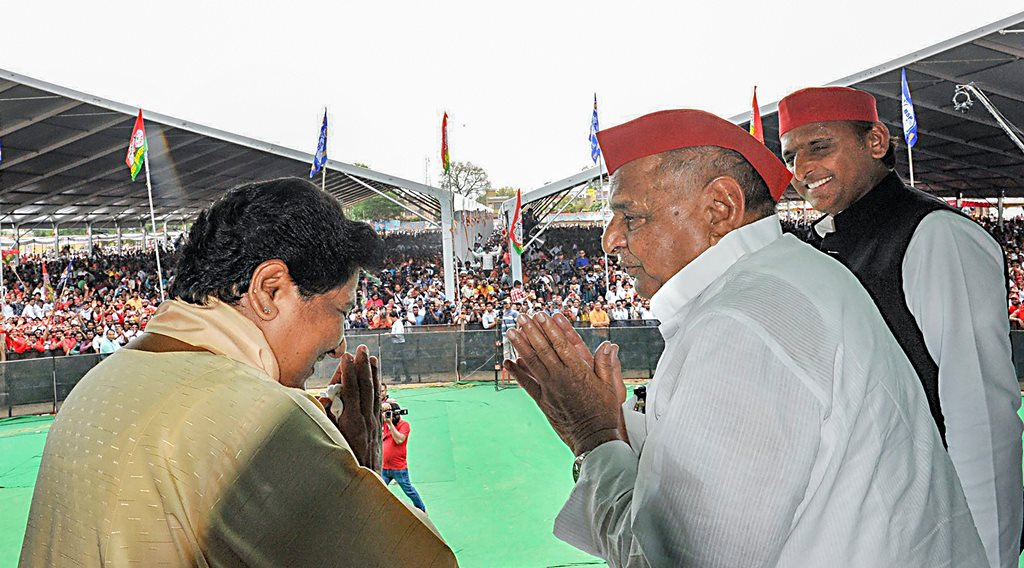 Mainpuri: Samajwadi Party patron Mulayam Singh Yadav exchanges greetings with Bahujan Samaj Party supremo Mayawati as SP President Akhilesh Yadav looks on during their joint election campaign rally in Mainpuri, Friday, April 19, 2019. Mulayam Singh Yadav and Mayawati have been bitter rivals since 1995 when SP cadres allegedly attacked the state guest house where the BSP chief had been camping with her supporters. (PTI Photo) (PTI4_19_2019_000087B)