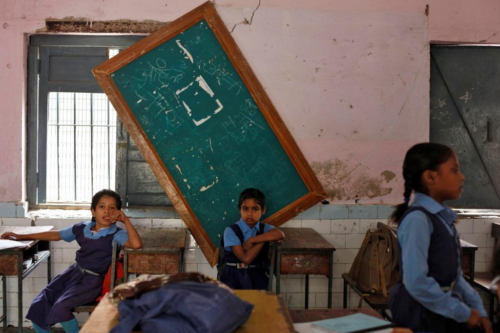 Schoolgirls sit inside their classroom before collecting their free mid-day meals, being distributed by a government-run primary school, in New Delhi May 8, 2013. India may soon pass a new law to give millions more people cheap food, fulfilling an election promise of the ruling Congress party that could cost about $23 billion a year and take a third of annual grain production. The National Food Security Bill, which aims to feed 70 percent of the population, could widen India's already swollen budget deficit next year, increasing the risk to its coveted investment-grade status. REUTERS/Mansi Thapliyal (INDIA - Tags: EDUCATION POLITICS FOOD) - RTXZEKN