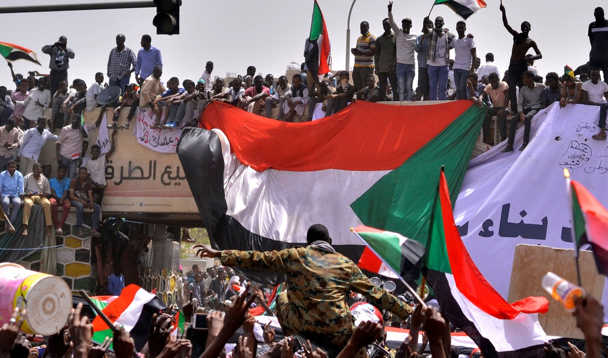 """A military officer is carried by the crowd as demonstrators chant slogans and carry their national flags, after Sudan's Defense Minister Awad Mohamed Ahmed Ibn Auf said that President Omar al-Bashir had been detained """"in a safe place"""" and that a military council would run the country for a two-year transitional period, outside Defence Ministry in Khartoum, Sudan April 11, 2019. REUTERS/Stringer"""