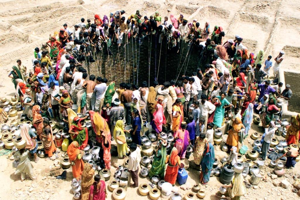 "People gather to get water from a huge well in the village of Natwarghad in the western Indian state of Gujarat on June 1, 2003. Natwargadh is in the midst of the worst drought in over a decade. Dams, wells and ponds have gone dry across the western and northern parts of Gujarat forcing people to wait for hours around village ponds for the irregular state-run water tankers to show up as the temperature sores to over 44 degree Celcius. The United Nation's World Environment Day will be celebrated on Thursday with the theme of ""Water - Two Billion People are Dying for It"". REUTERS/Amit Dave BEST QUALITY AVAILABLE"