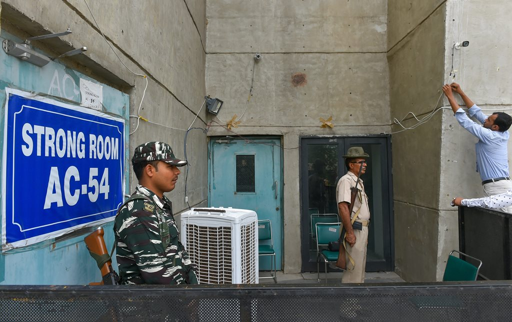 New Delhi: Security personnel stand guard outside a strongroom, where Electronic Voting Machines's (EVM) are kept after the last phase of Lok Sabha polls, at Akshardham in New Delhi, Wednesday, May 22, 2019. (PTI Photo/ Kamal Kishore) (PTI5_22_2019_000025B)