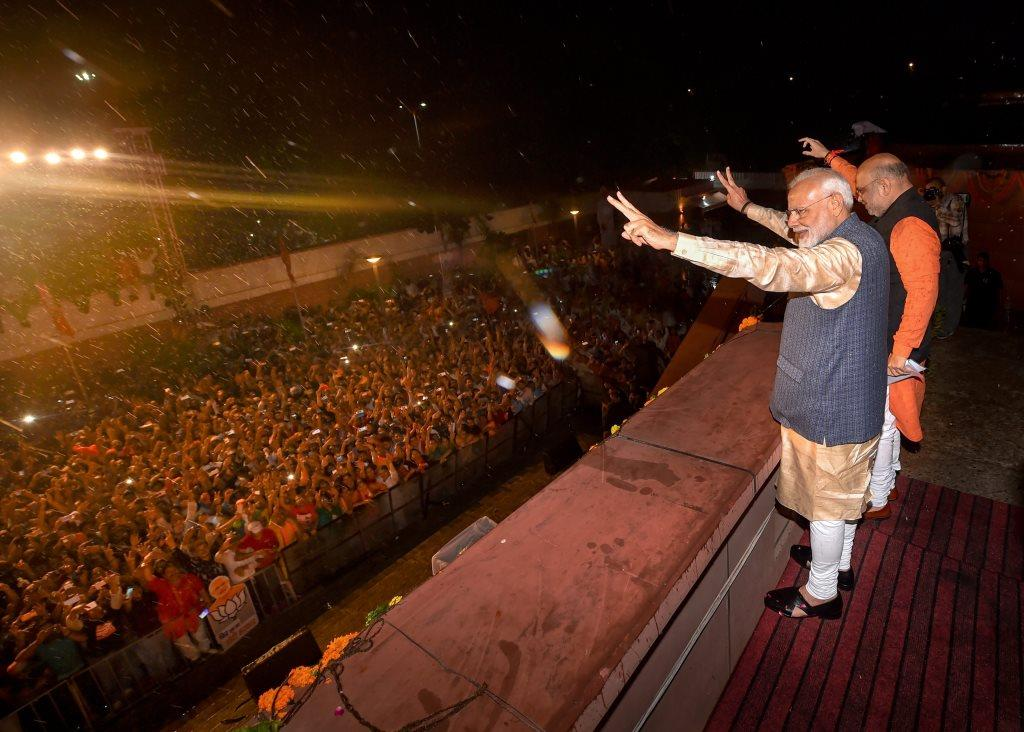New Delhi: Bhartiya Janata Party workers welcome Prime Minister Narendra Modi as he, along with BJP President Amit Shah, arrives at the party headquarters to celebrate the party's victory in the 2019 Lok Sabha elections, in New Delhi, Thursday, May 23, 2019. (PTI Photo/Manvender Vashist) (PTI5_23_2019_000482B)