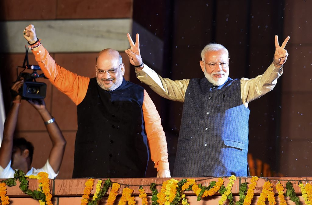 New Delhi: Bhartiya Janata Party workers welcome Prime Minister Narendra Modi as he, along with BJP President Amit Shah, arrives at the party headquarters to celebrate the party's victory in the 2019 Lok Sabha elections, in New Delhi, Thursday, May 23, 2019. (PTI Photo/Manvender Vashist) PTI5_23_2019_000477B