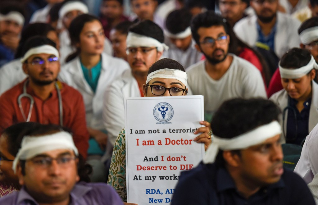 New Delhi: Members of Resident Doctors Association (RDA) of AIIMS wearing bandages on their heads protest to show solidarity with their counterparts in West Bengal, who stopped work on Tuesday protesting against the assault on their colleagues, in New Delhi, Friday, June 14, 2019. (PTI Photo/Kamal Singh)(PTI6_14_2019_000024B)