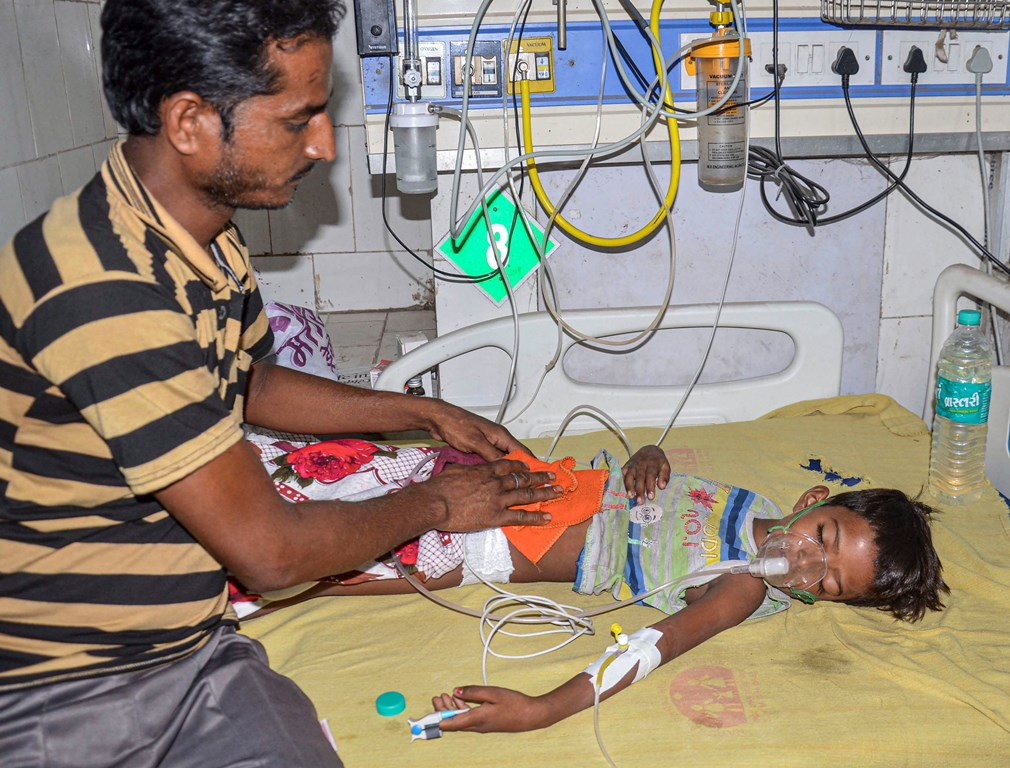 Muzaffarpur: A man takes care of a child suffering from Acute Encephalitis Syndrome (AES) at a hospital in Muzaffarpur, Thursday, June 13, 2019. Bihar's Muzaffarpur district is reeling under an outbreak of the disease, taking the death toll this month to atleast 43 children. (PTI Photo)(PTI6_13_2019_000115B)
