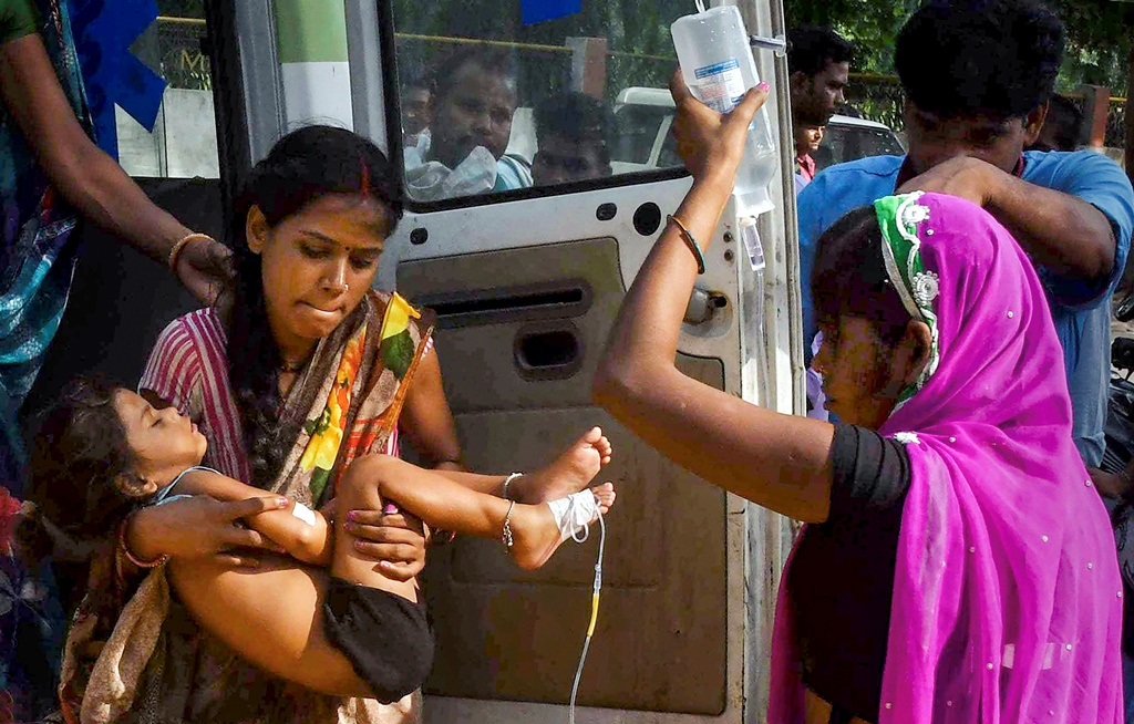 Muzaffarpur: A woman carrying a child showing symptoms of Acute Encephalitis Syndrome (AES) arrives at Shri Krishna Medical College and hospital for treatment, in Muzaffarpur, Sunday, June 16, 2019. With one more death of a child on Sunday morning, the death toll in the district rose to 83 this month. (PTI Photo) (PTI6_16_2019_000043B)