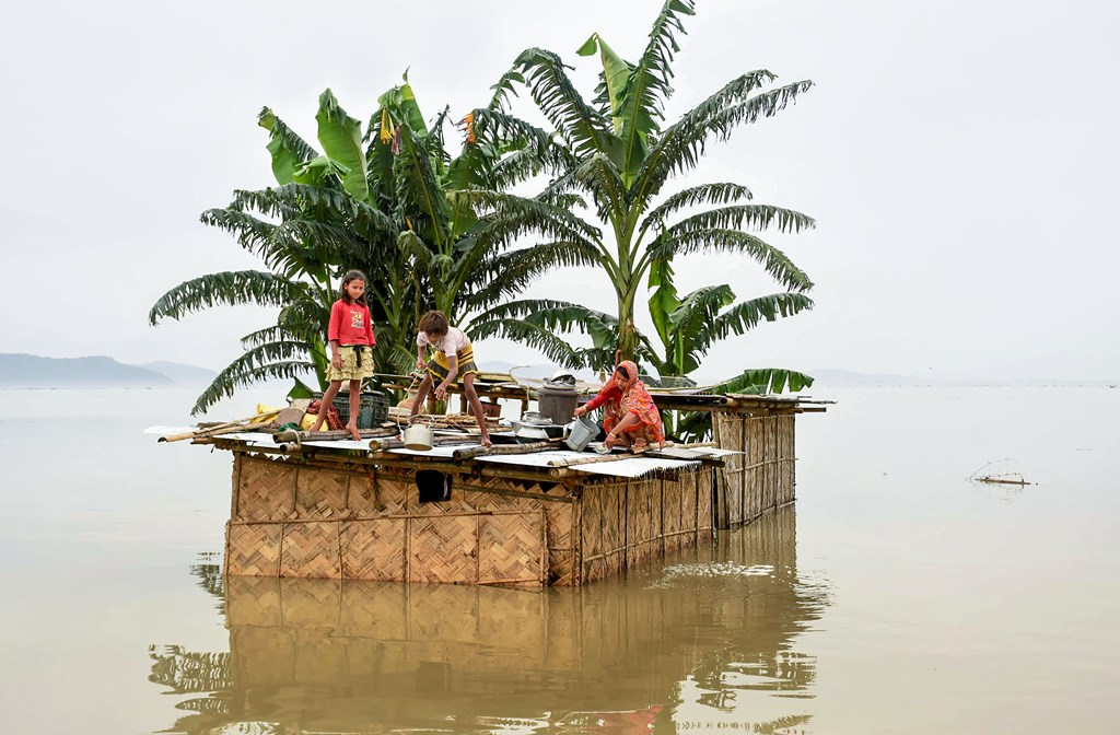 Kamrup: A family marooned on the top of a hut in the flood-hit locality of Panikhaiti in Kamrup district of Assam, Monday, July 15, 2019. (PTI Photo) (PTI7_15_2019_000212B)