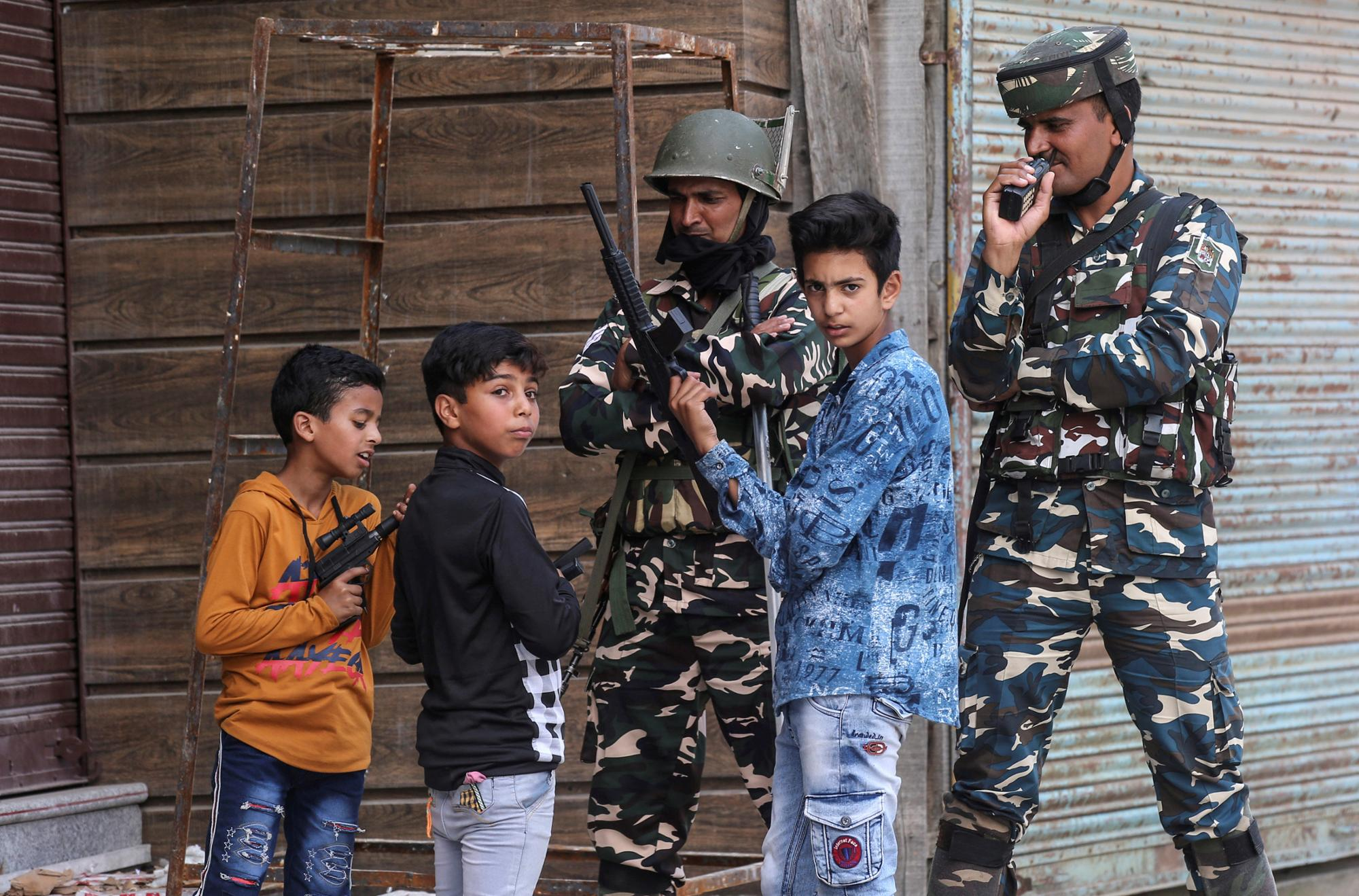 Children play with toy guns next to Indian security force personnel during restrictions after the scrapping of the special constitutional status for Kashmir by the government, in Srinagar, August 13, 2019. REUTERS/Danish Ismail