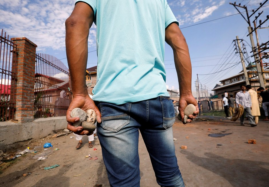 A Kashmiri man holds stones during clashes with Indian security forces, after scrapping of the special constitutional status for Kashmir by the Indian government, in Srinagar, August 23, 2019. REUTERS/Adnan Abidi