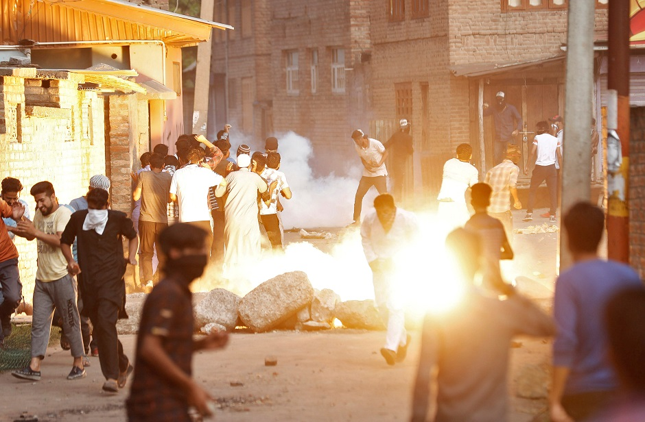 Kashmiris run for cover as a teargas shell fired by Indian security forces explodes during clashes. PHOTO: REUTERS