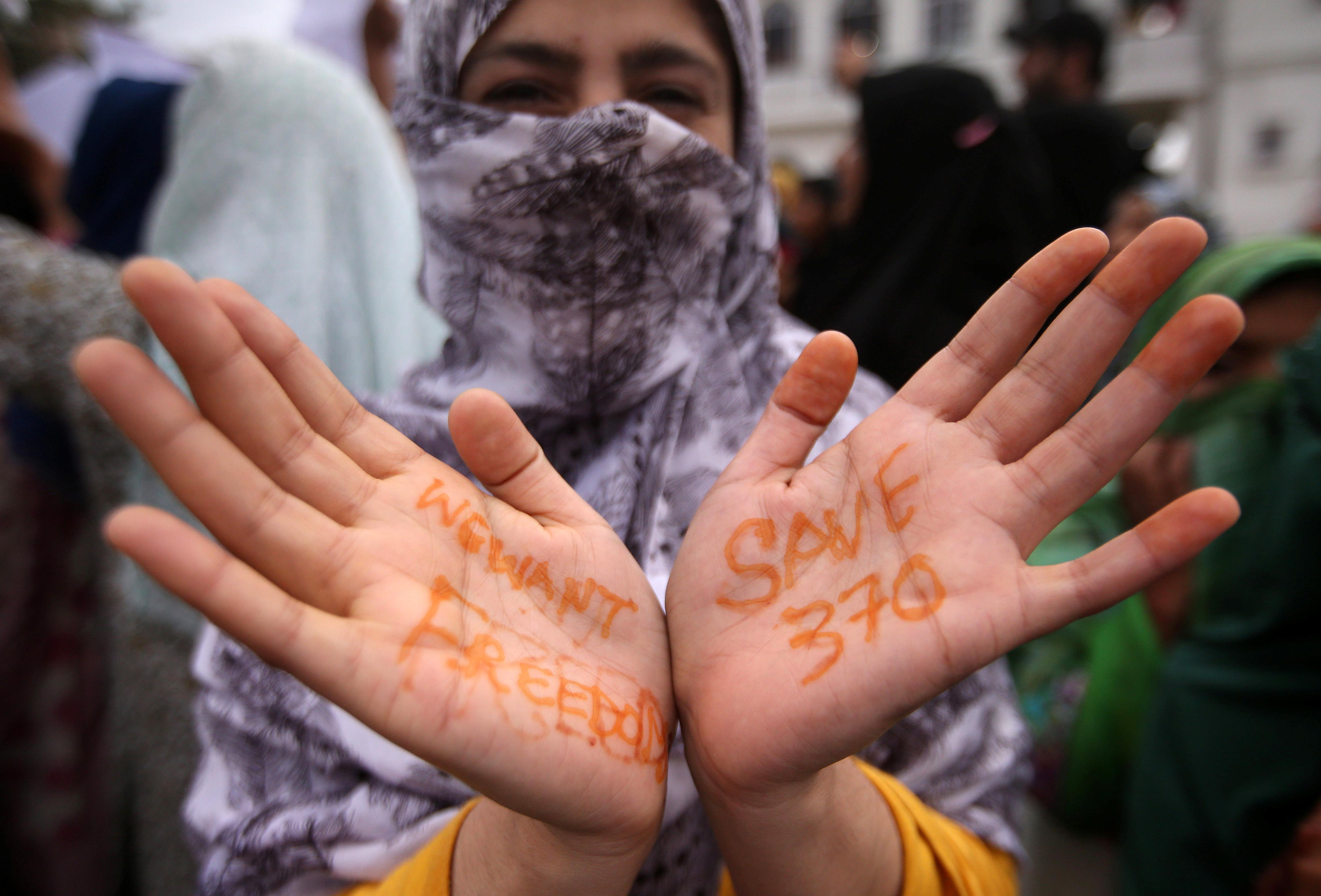 A Kashmiri woman shows her hand with a message as others shout slogans during a protest after the scrapping of the special constitutional status for Kashmir by the Indian government, in Srinagar, August 11, 2019. REUTERS/Danish Siddiqui