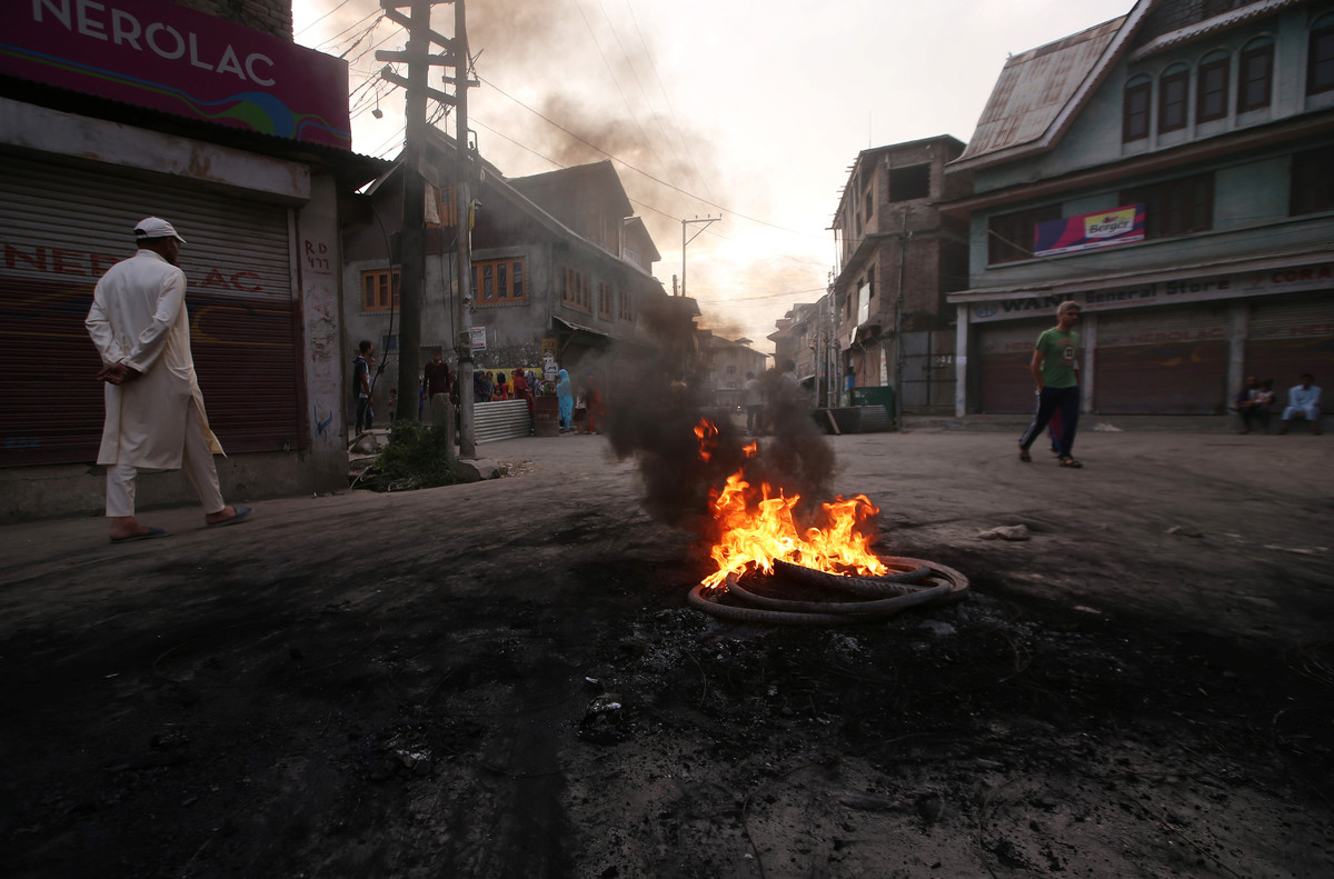 Kashmiri people walk past burning tyres during a protest after the scrapping of the special constitutional status for Kashmir by the Indian government, in Srinagar, August 27, 2019. Picture taken on August 27, 2019. REUTERS/Danish Ismail