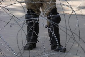 An Indian police officer stands behind the concertina wire during restrictions on Eid-al-Adha after the scrapping of the special constitutional status for Kashmir by the Indian government, in Srinagar, August 12, 2019. REUTERS/Danish Ismail
