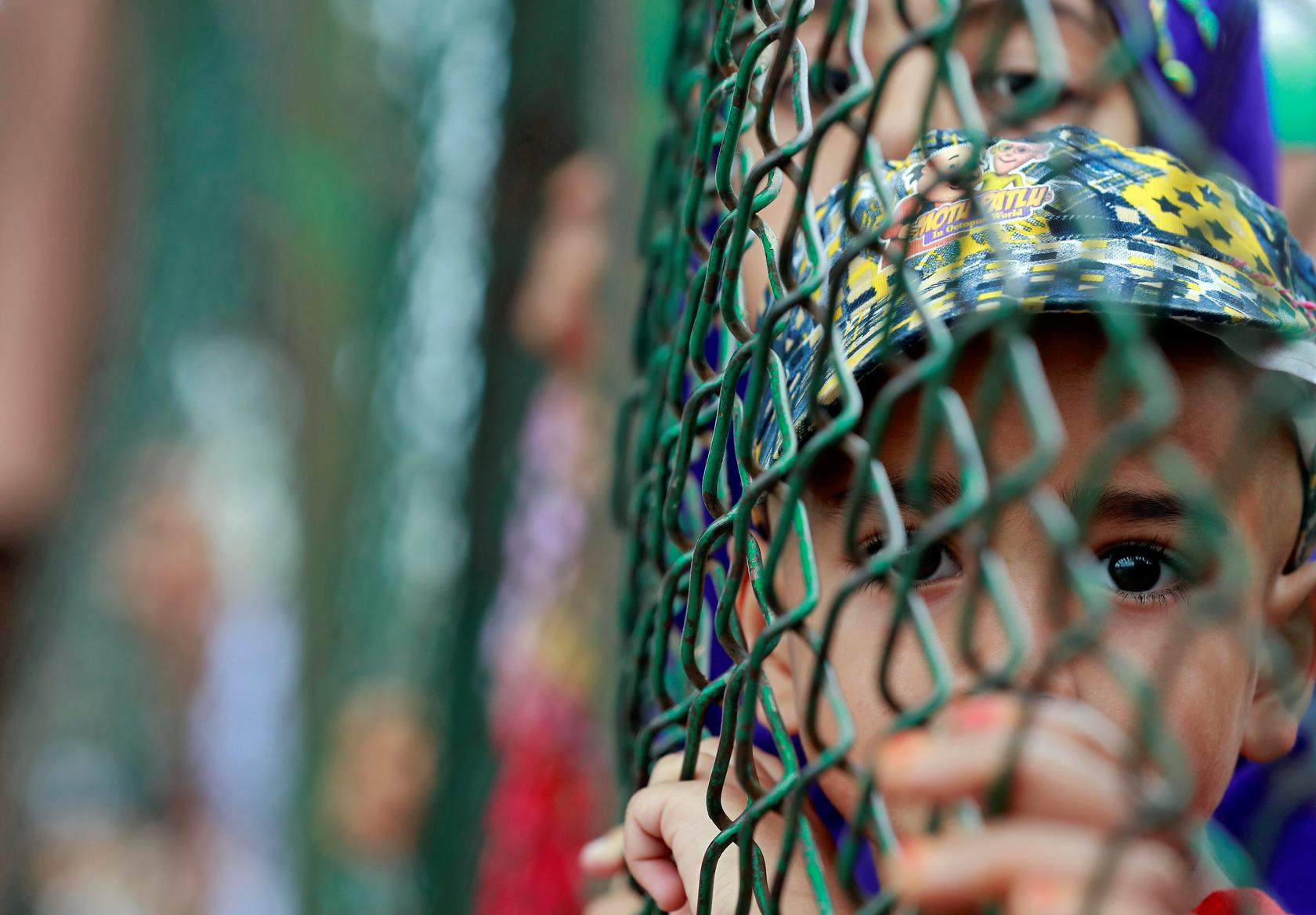 Kashmiri child looks from behind a fence at a protest site after Friday prayers during restrictions after the Indian government scrapped the special constitutional status for Kashmir, in Srinagar, August 16, 2019. REUTERS/Danish Ismail