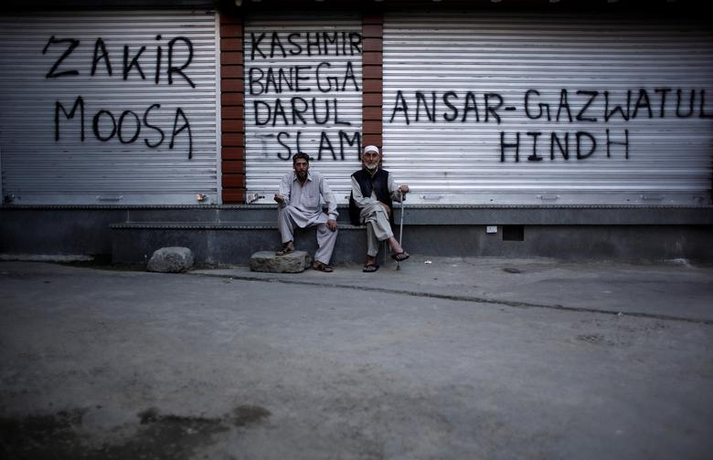 Kashmiri men sit in front of the closed shops painted with graffiti during restrictions after scrapping of the special constitutional status for Kashmir by the Indian government, in Srinagar, August 20, 2019. REUTERS/Adnan Abidi