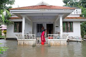 A woman clears out the water from her flooded house at Paravur on the outskirts of Kochi, in Kerala, India August 11, 2019. REUTERS/Sivaram V