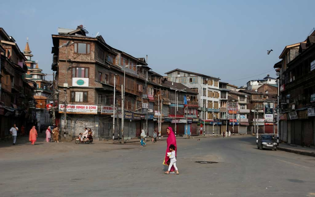Residents cross a street during restrictions in Srinagar. (Photo:Reuters)