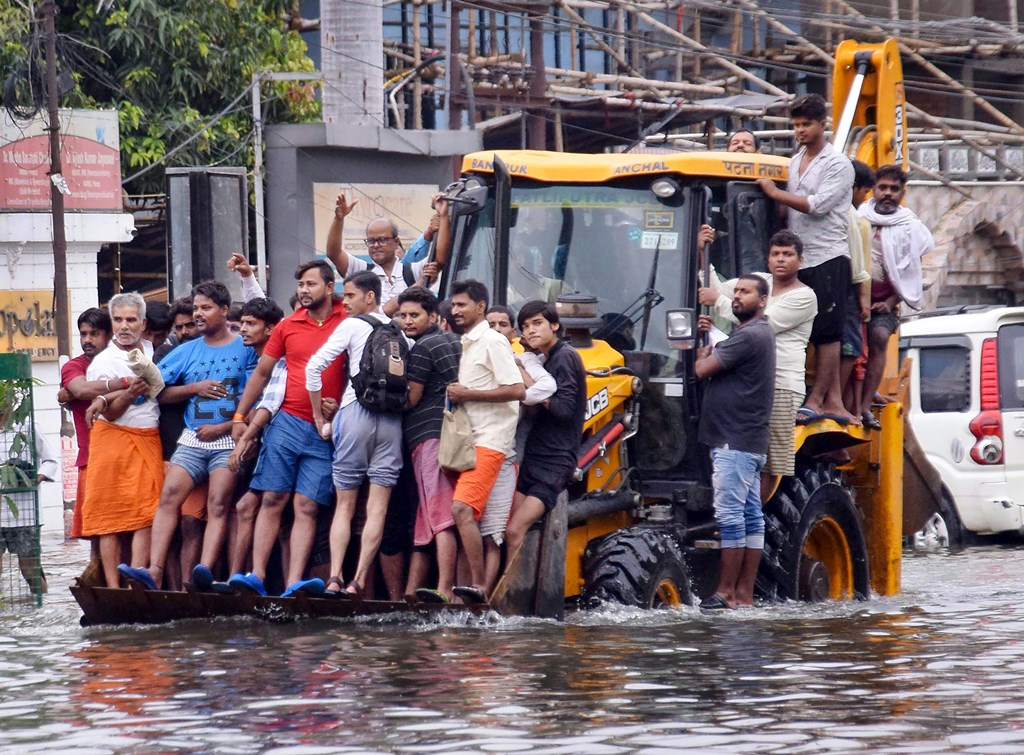 Patna: Residents ride a municipality earth-mover through a flooded street following heavy monsoon rain, in Patna, Monday, Sept. 30, 2019. (PTI Photo)(PTI9_30_2019_000128B)