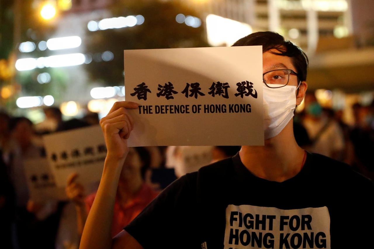 A man covers his eye with a placard as he attends a protest in Hong Kong, China August 30, 2019. REUTERS/Kai Pfaffenbach