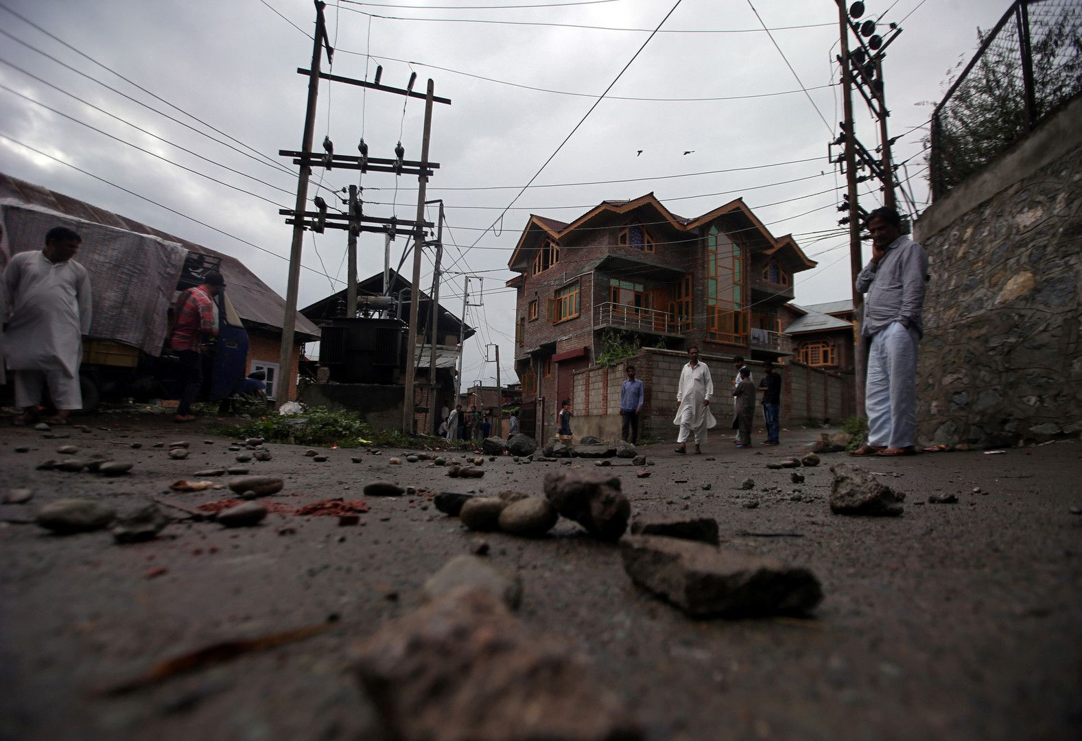 People walk on a road covered with stones and pieces of brick during restrictions in Srinagar, August 14. REUTERS/Danish Ismail