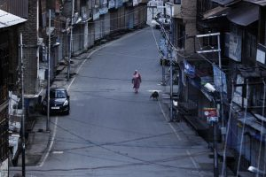A Kashmiri woman walks on a deserted road during restrictions, after scrapping of the special constitutional status for Kashmir by the Indian government, in Srinagar, August 25, 2019. Picture taken on August 25, 2019. REUTERS/Adnan Abidi