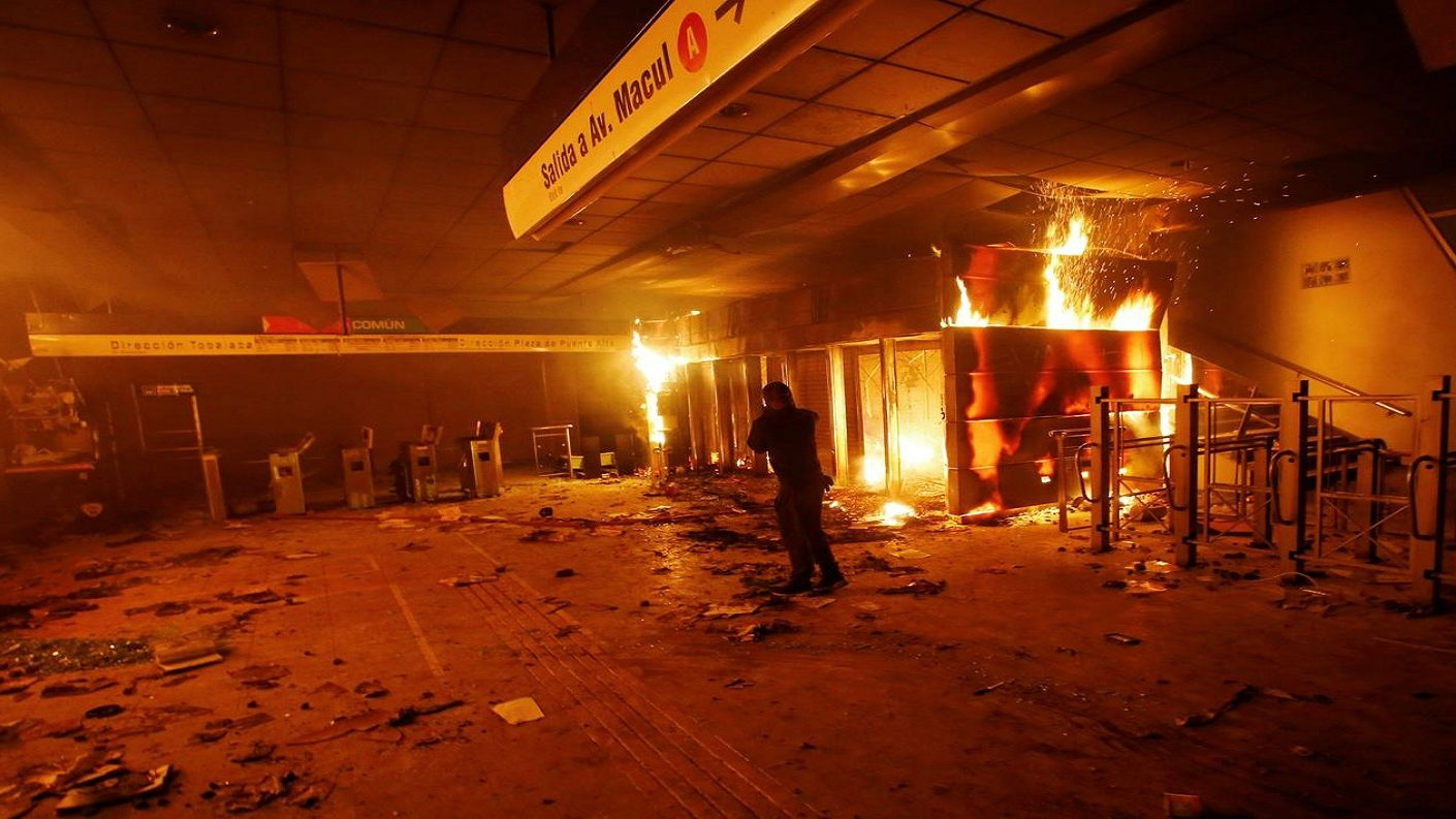 A subway ticket office is seen on fire during a protest against the increase in the subway ticket prices in Santiago, Chile, October 19, 2019. (Ramon Monroy/ Reuters)